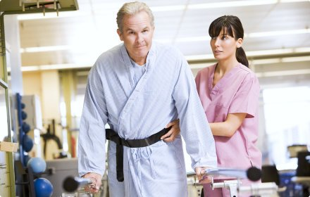 nurse and elderly man doing physical therapy