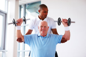nurse and elderly man doing physical exercise